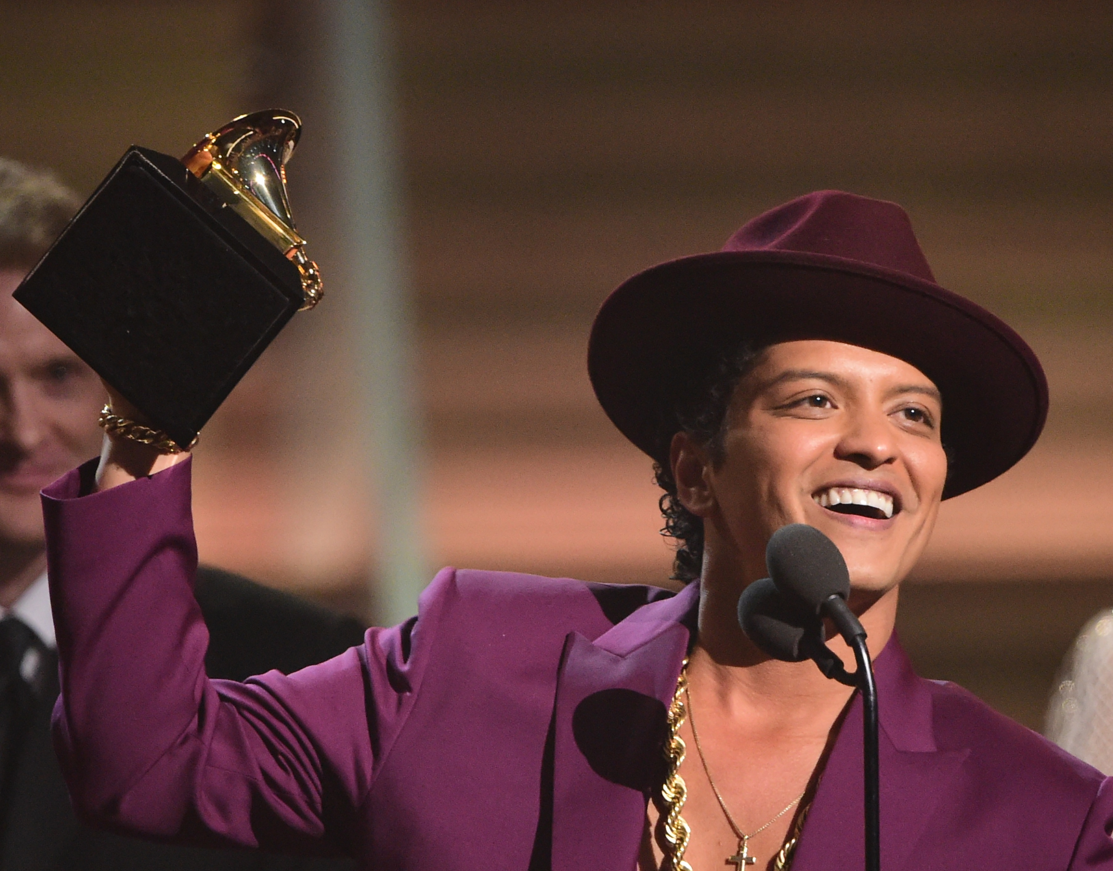 TOPSHOT - Singer Bruno Mars holds up the award for the Record of the Year, Uptown Funk onstage during the 58th Annual Grammy music Awards in Los Angeles February 15, 2016. AFP PHOTO/ ROBYN BECK / AFP / ROBYN BECK (Photo credit should read ROBYN BECK/AFP/Getty Images)
